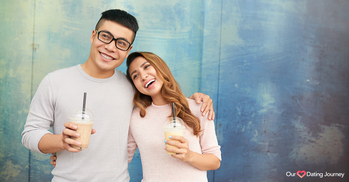 Happy Asian couple holding drinks