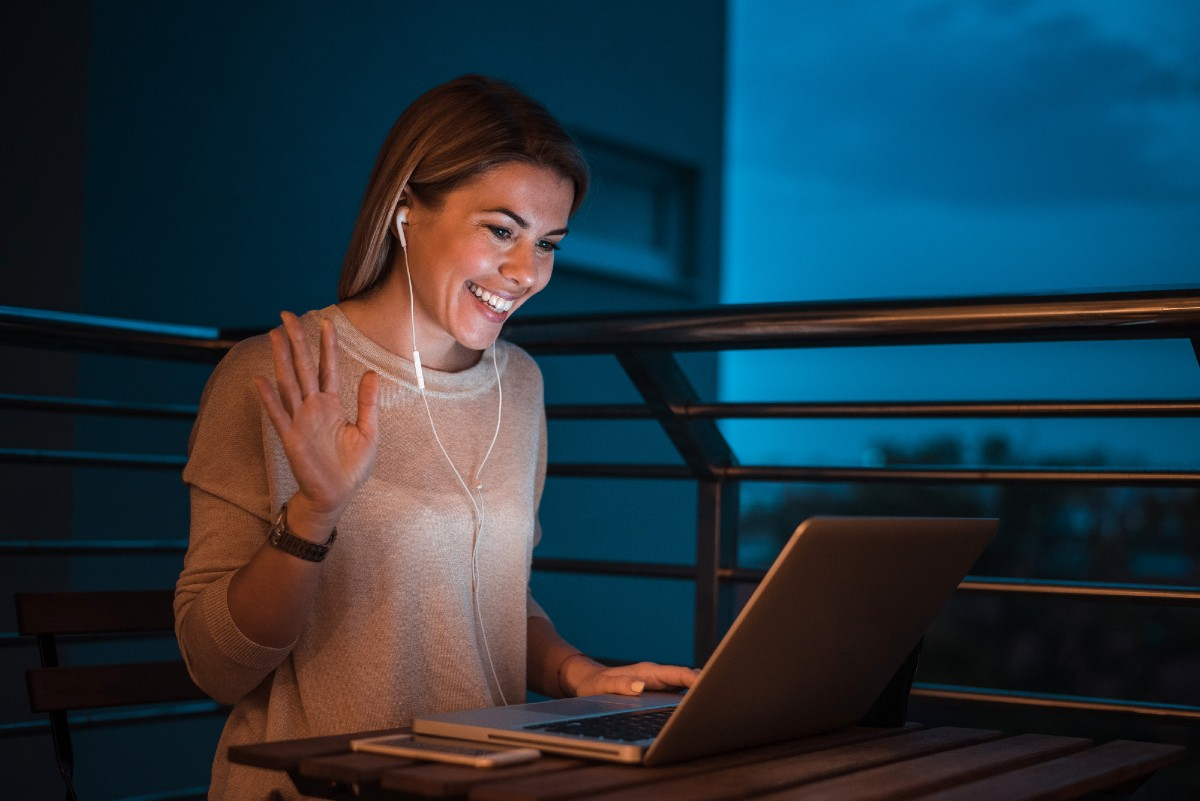 Young smiling woman having a video call using laptop at night